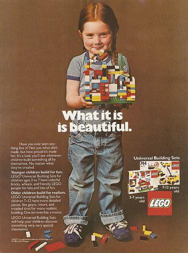 Little girl in traditionally boyish clothes grinning with her legos. Text overlay reads 'what it is is beautiful.'