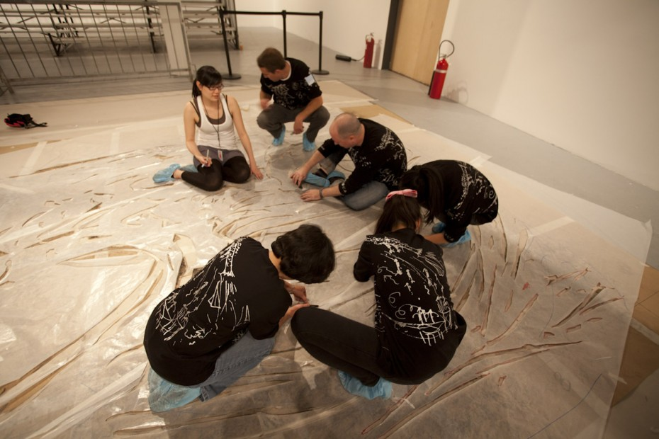 Cai Studio assistant with volunteers cutting glassine paper to create Chaos in Nature, Los Angeles, 2012, photo by Joshua White, courtesy The Museum of Contemporary Art, Los Angeles