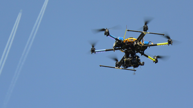 An octocopter drone hovers in front of vapor trails left by aircrafts during a demonstration. REUTERS/Srdjan Zivulovic