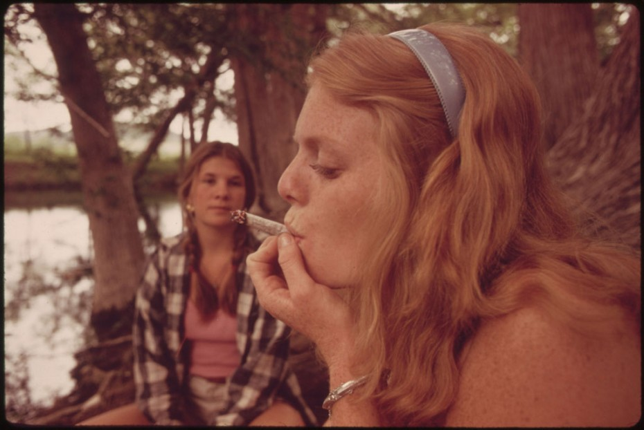 """One Girl Smokes Pot While Her Friend Watches During an Outing in Cedar Woods near Leakey, Texas.""  May, 1973. U.S. National Archives. Photographer: Marc St. Gil."