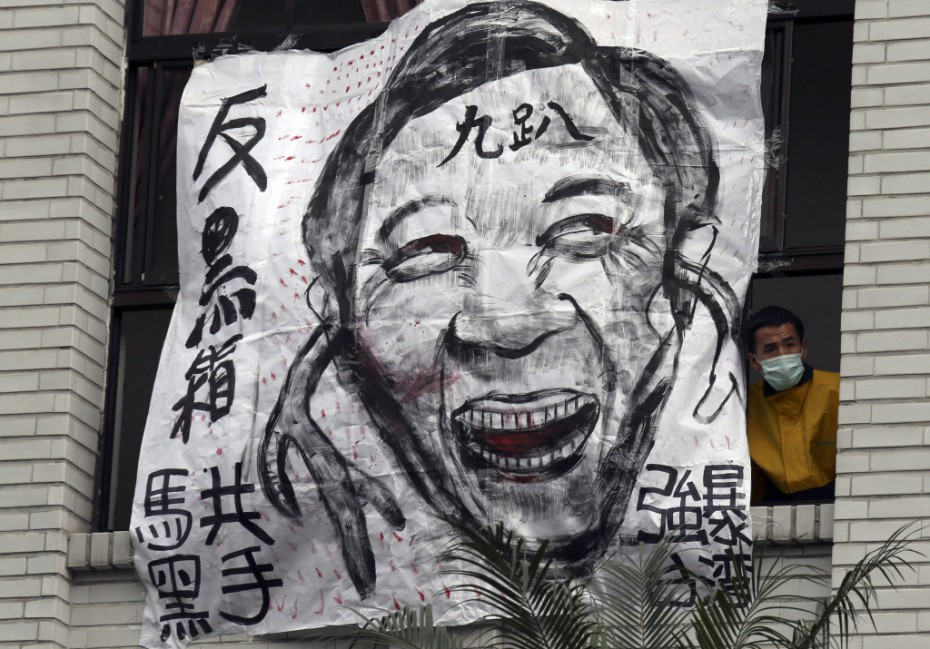 "A protester looks out from a window next to a cartoon depicting Taiwan's President Ma Ying-jeou at Taiwan's legislature in Taipei, March 21, 2014. The Chinese characters on the cartoon read, ""Anti-black box"" (top, L), ""Communist Ma the black hand"" (bottom, L), ""Rape Taiwan"" (R) and ""Nine percent approval rating""  Photo: Reuters/Patrick Lin."