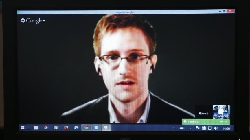 "Edward Snowden is seen on a screen as he speaks via video conference with members of the Committee on Legal Affairs and Human Rights of the Parliamentary Assembly of the Council of Europe during an hearing on ""mass surveillance"" in Strasbourg, April 8, 2014."