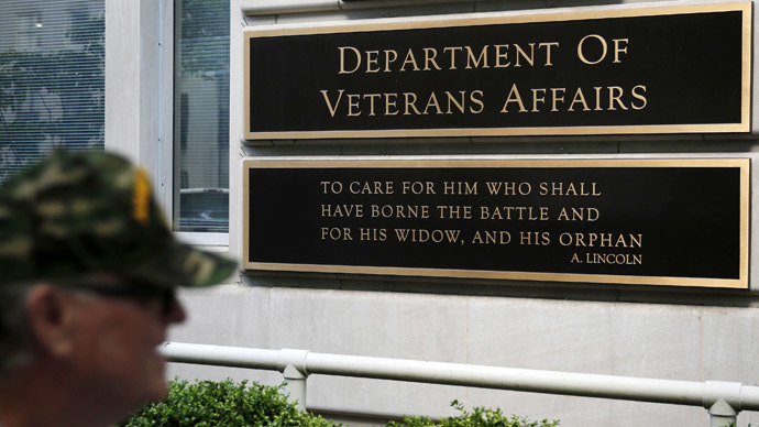The sign in the front of the headquarters building at the Department of Veteran Affairs is seen as a man walks past in Washington. (Reuters/Larry Downing)