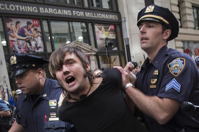 New York City police officers arrest a man taking part in the Flood Wall Street demonstration in Lower Manhattan, New York September 22, 2014. Hundreds of protesters marched through New York City's financial district on Monday to call attention to what organizers say is capitalism's contribution to climate change, snarling traffic and risking arrest as they sought to block Wall Street. The Flood Wall Street demonstration comes on the heels of Sunday's international day of action that brought some 310,000 people to the streets of New York City in the largest single protest ever held over climate change. REUTERS/Adrees Latif