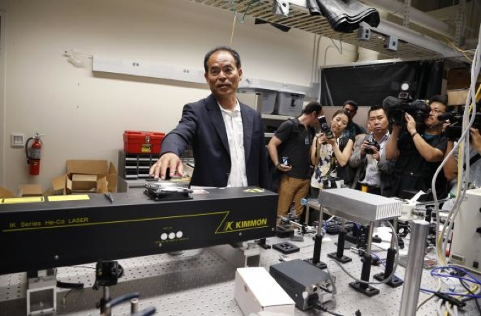 Japanese-born U.S. citizen Shuji Nakamura talks about a laser in a lab after winning the 2014 Nobel Prize for Physics, at the University of California Santa Barbara in Isla Vista, California October 7, 2014. [Reuters]