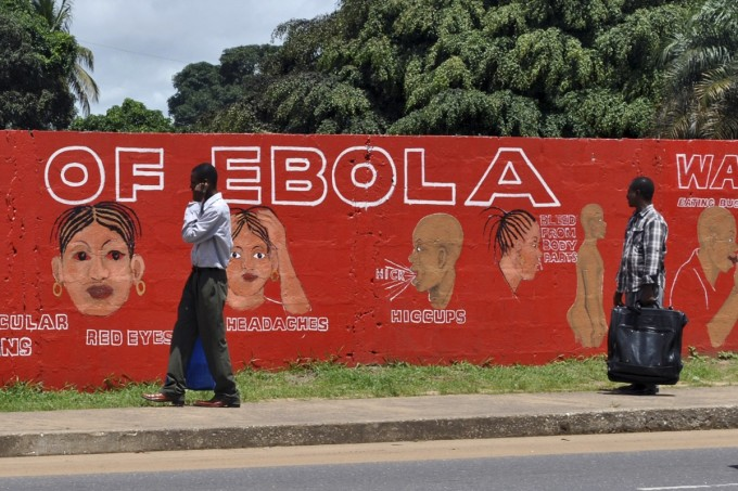 Pedestrians walk past a mural showing the symptoms of the Ebola virus in Monrovia