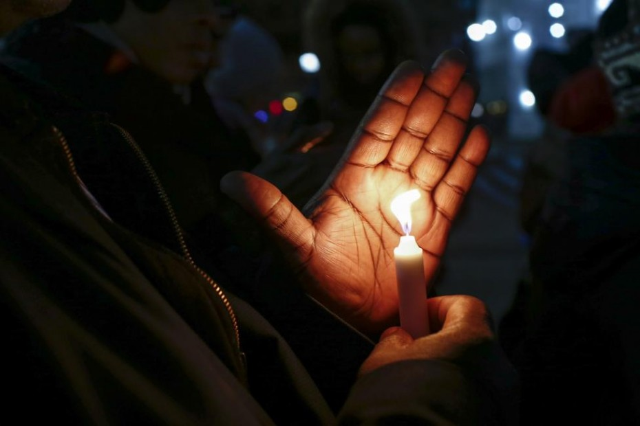 People hold candles while they take part in a rally to call for action in response to police violence, at the steps of City Hall in New York, December 12, 2014. Photo: Reuters