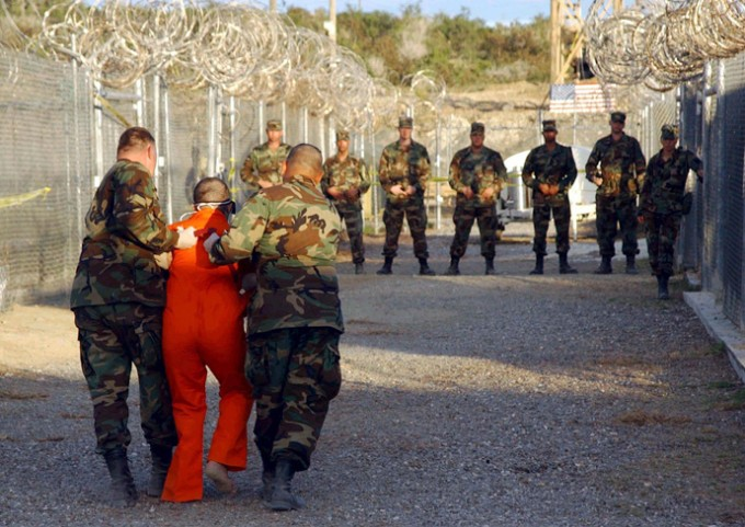 U.S. Army Military Police escort a detainee to his cell during in-processing to the temporary detention facility at Camp X-Ray in Naval Base Guantanamo Bay (Reuters)